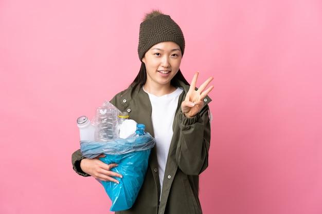 Chinesisches mädchen, das eine tasche voller plastikflaschen hält, um auf lokalisiertem rosa glücklich zu recyceln und drei mit den fingern zu zählen