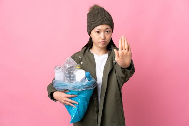 Chinesisches mädchen, das eine tasche voller plastikflaschen hält, um auf lokalisiertem rosa zu recyceln, das stoppgeste macht