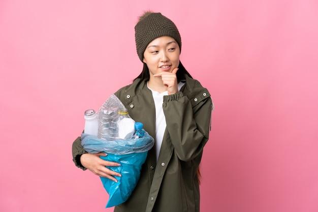 Chinesisches mädchen, das eine tasche voller plastikflaschen hält, um auf lokalisiertem rosa zu recyceln, das zur seite schaut und lächelt
