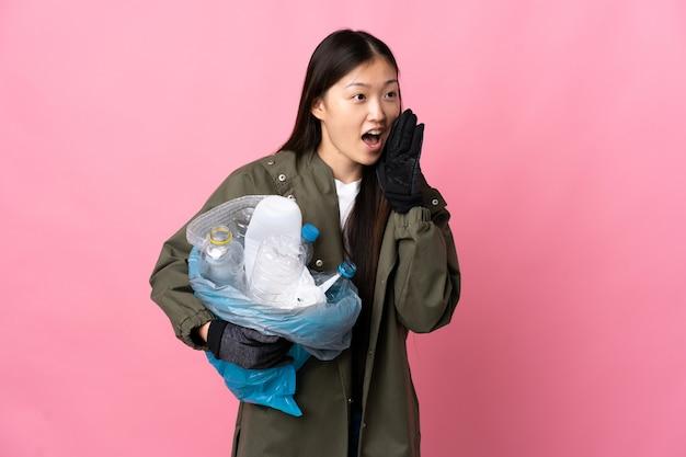 Chinesisches mädchen, das eine tasche voller plastikflaschen hält, um über isolierte rosa wand zu recyceln, die mit dem mund weit offen zur seite schreit