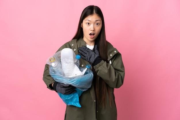 Chinesisches mädchen, das eine tasche voller plastikflaschen hält, um über rosa überrascht und schockiert zu recyceln, während es richtig schaut