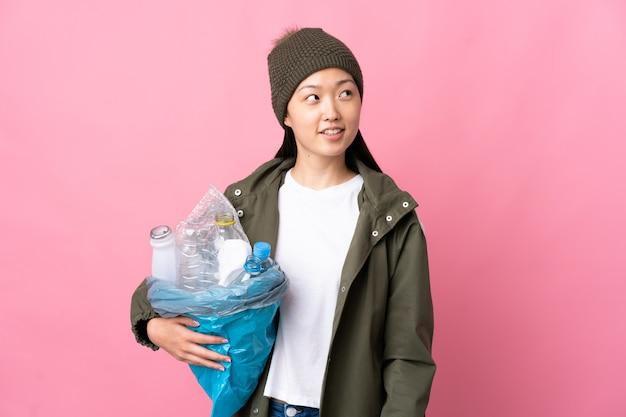 Chinesisches mädchen, das eine tasche voller plastikflaschen hält, um zu recyceln