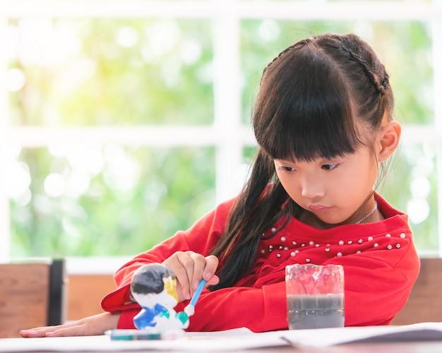 Chinesisches mädchen malt auf einer puppe im klassenzimmer
