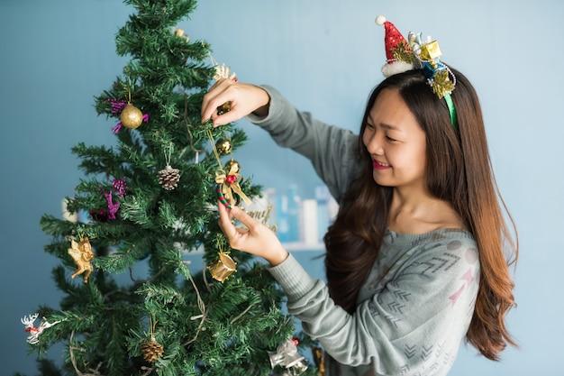 Chinesisches mädchen verzieren geschenk auf weihnachtsbaum