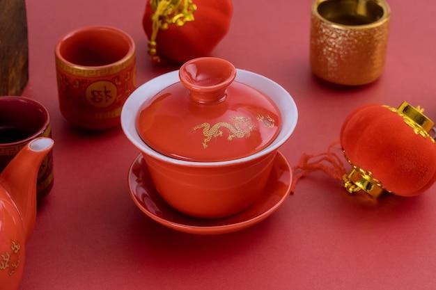 Chinesisches neujahr des traditionellen teezubehörfestivaldekorations in behältermandarinen auf einem rot