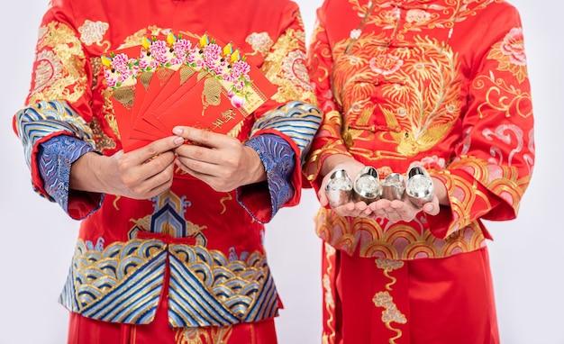 Chinesisches neujahr, geschenkgeld und bargeld werden bekommen - geben sie männern und frauen, die cheongsam für traditionelle tragen