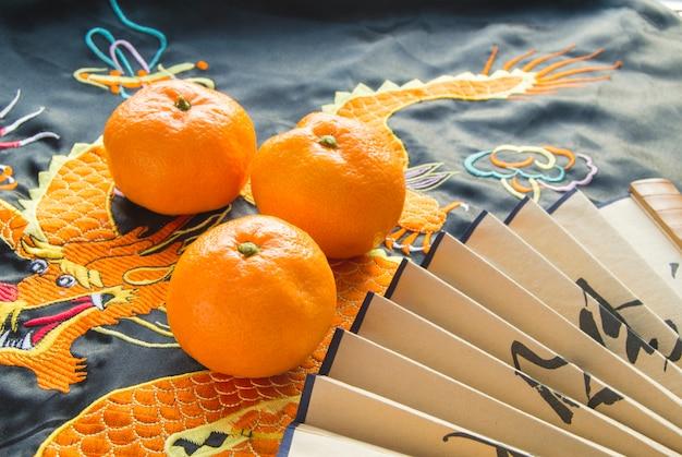 Chinesisches neujahr, mandarinen und ein fächer auf dem seidenstoff mit einem gestickten drachen