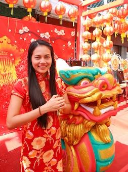 Chinesisches neujahr. schöner junger asiatischer frauenkleid traditioneller cheongsam gruß.