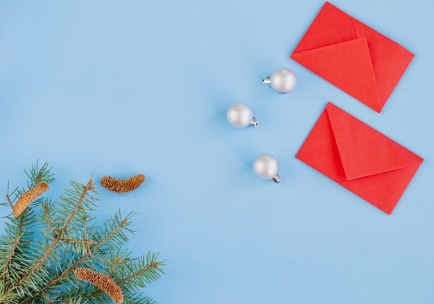 Chinesisches neujahr und neues mondjahr. zweige der fichte, rote umschläge mit taschengeld. weihnachtsdekorationen, gewürze auf blau. flache position, draufsicht, copyspace