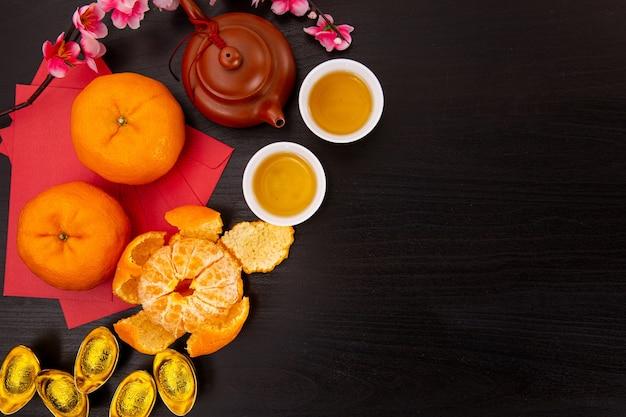 Chinesisches neujahrs-mandarinen- und teewasser mit draufsicht