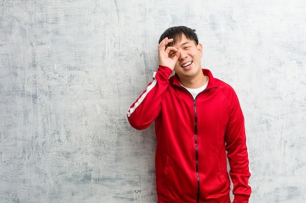 Chinesisches überzeugtes handeln der jungen sporteignung okaygeste auf auge