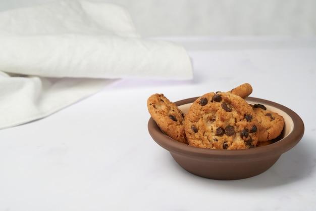 Chip schokoladenplätzchen auf einer tonschale mit weißem hintergrund und wischen