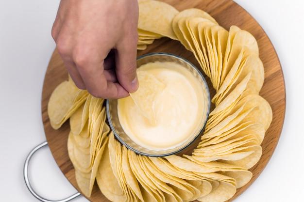 Chips auf einem hölzernen brett mit soße, männliche hand mit chips