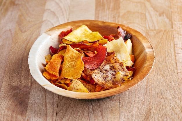 Chips aus naturprodukten, rüben, kartoffeln, karotten, süßkartoffeln in einem holzteller, auf einem holz.