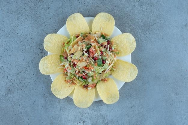 Chips, die eine portion käse- und gemüsesalat auf marmortisch umgeben.