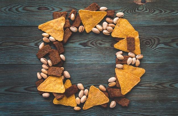 Chips, gesalzene cracker und pistazien auf einem blauen holz.