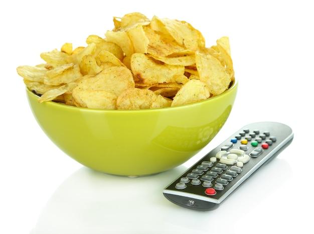 Chips in schüssel und tv-fernbedienung isoliert auf weiß Premium Fotos