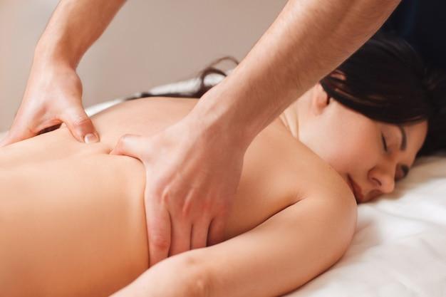 Chiropraktiker, der frau mit rückenschmerzen behandelt