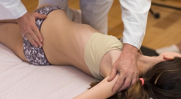 Chiropraktiker, masseur, der einen jungen patienten behandelt