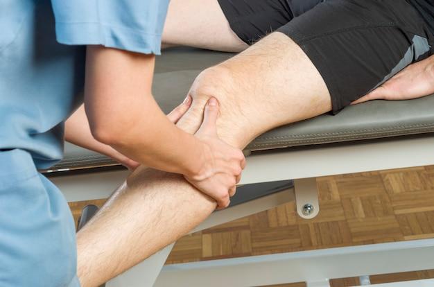 Chiropraktiker / physiotherapeut, der eine kniemassage durchführt