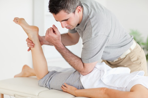 Chiropraktiker streckt das bein einer frau