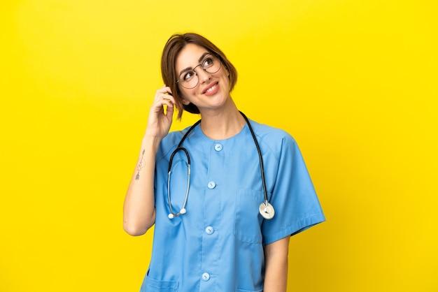 Chirurg arzt frau auf gelbem hintergrund isoliert denken eine idee