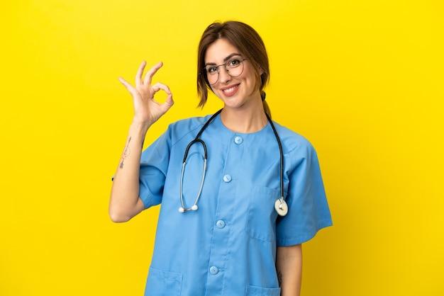 Chirurg arzt frau auf gelbem hintergrund isoliert zeigt ok zeichen mit den fingern
