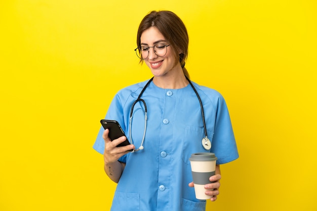 Chirurg arzt frau isoliert auf gelbem hintergrund mit kaffee zum mitnehmen und einem handy