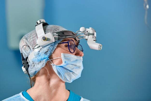 Chirurg, der chirurgie im krankenhausoperationsraum durchführt. chirurg in tragenden lupen der maske während des medizinischen procadure.