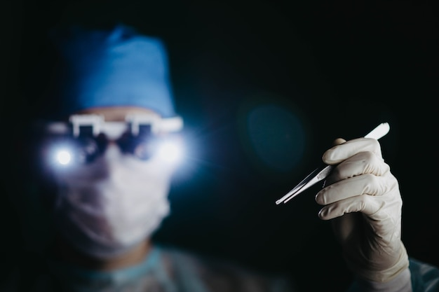 Chirurg, der eine binokulare lupe trägt, operiert einen patienten in einem dunklen operationssaal