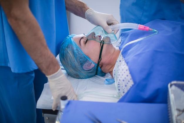 Chirurg, der einem patienten sauerstoffmaske aufsetzt