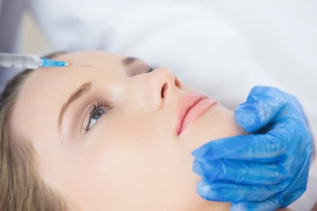 Chirurg, der einspritzung auf stirn auf dem ruhigen frauenlügen macht