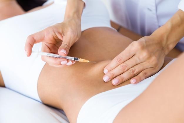 Chirurg, der einspritzung in weiblichen körper macht. fettabsaugung konzept.