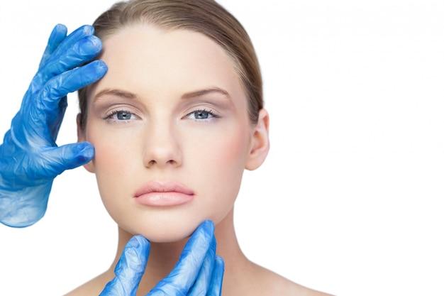 Chirurg, der ernstes hübsches modell überprüft