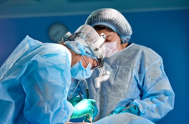Chirurg, der kosmetische chirurgie im operationssaal des krankenhauses durchführt. chirurg in der maske, die lupen während der medizinischen prozedur trägt. brustvergrößerung