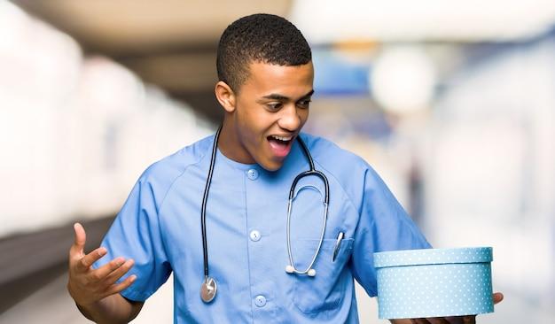 Chirurg doktormann, der geschenkbox in den händen in einem krankenhaus hält
