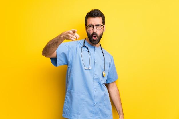 Chirurg doktormann frustriert durch eine schlechte situation und zeigt auf die front