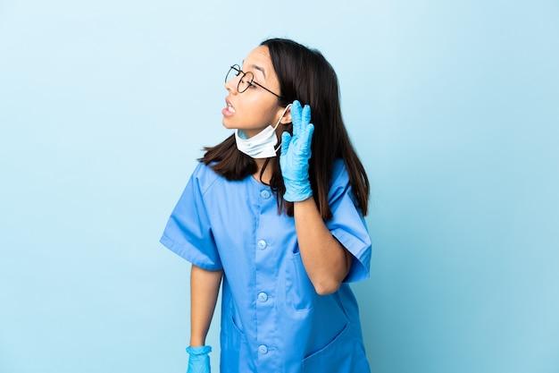 Chirurg frau über blaue wand, die etwas hört, indem sie hand auf das ohr legt