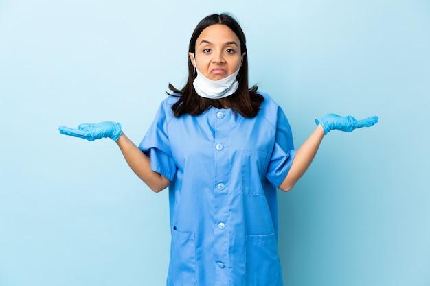 Chirurg frau über blaue wand, die zweifel beim anheben der hände hat