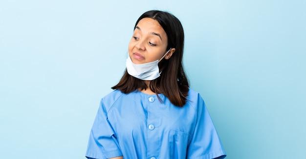 Chirurg frau über isolierte blaue wand, die zweifel beim betrachten der seite hat
