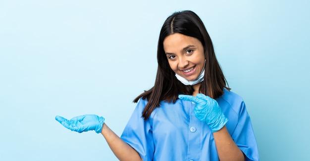 Chirurg frau über isolierte blaue wand hält copyspace imaginär auf der handfläche, um eine anzeige einzufügen