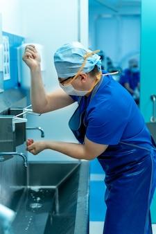 Chirurg im krankenhaus wäscht sich vor einer operation gründlich die hände.
