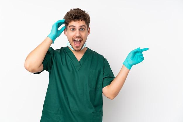 Chirurg in grüner uniform an weißer wand überrascht und finger zur seite zeigend
