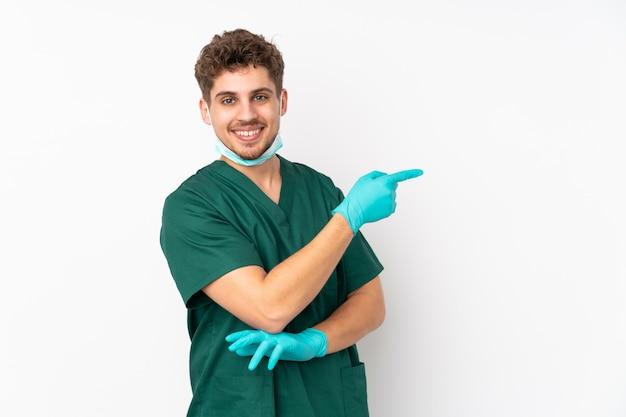 Chirurg in grüner uniform auf isolierter weißer wand, die finger zur seite zeigt
