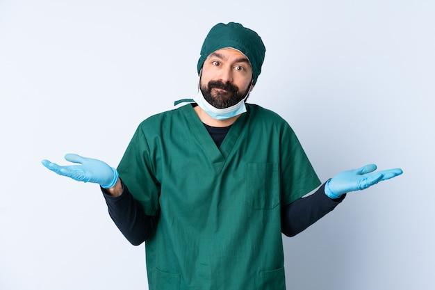 Chirurg mann in der grünen uniform über isolierter wand, die zweifel beim anheben der hände hat