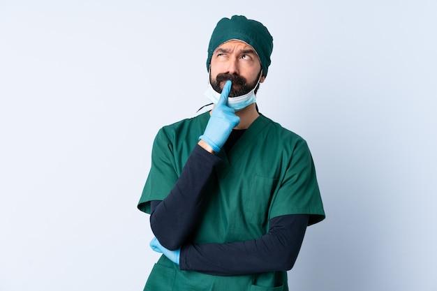 Chirurg mann in der grünen uniform über isolierter wand, die zweifel beim aufblicken hat