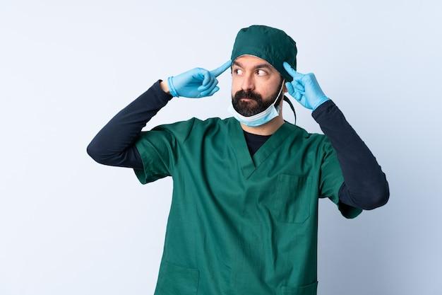 Chirurg mann in der grünen uniform über isolierter wand, die zweifel und denken hat