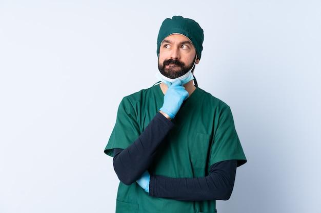 Chirurg mann in grüner uniform über mauer mit zweifeln und denken