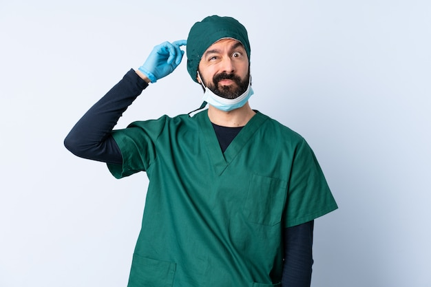 Chirurg mann in grüner uniform über mauer mit zweifeln