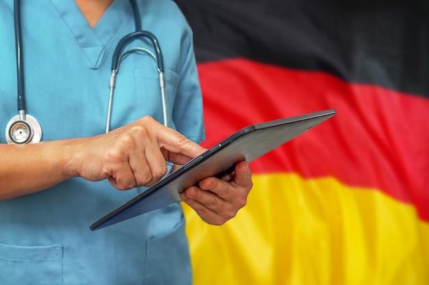 Chirurg oder arzt, der ein digitales tablett auf dem hintergrund der deutschlandflagge verwendet